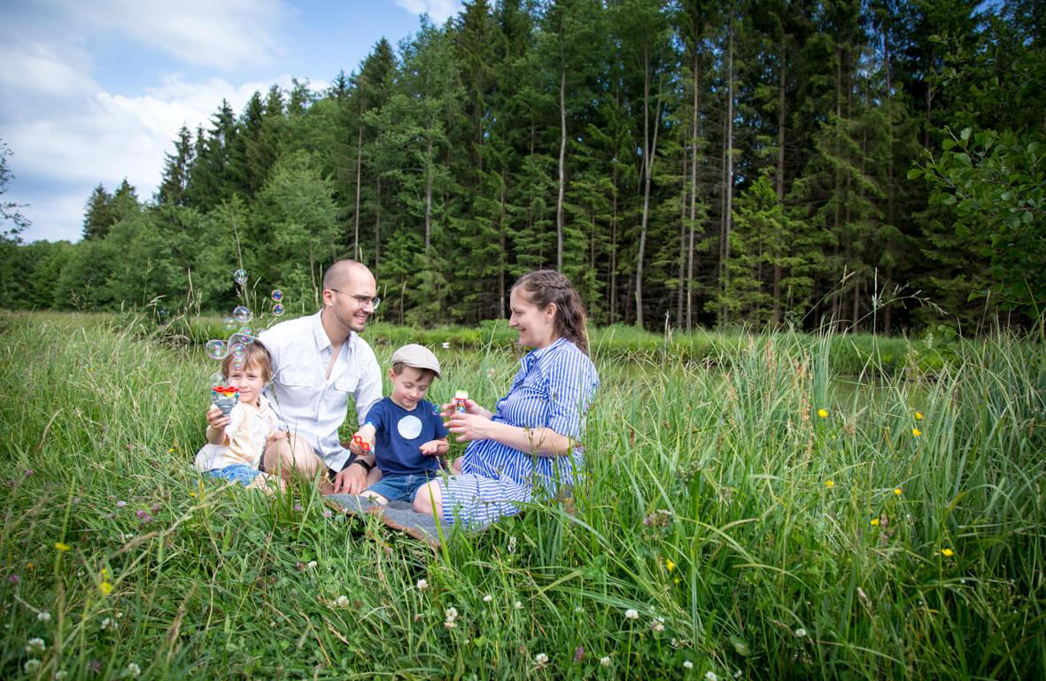 Familie in der Natur mit Seifenblasen; Familienfotografie