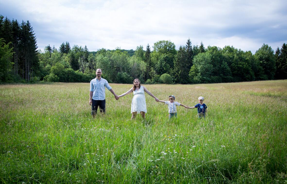 Familie hält sich an der Hand, in der Natur