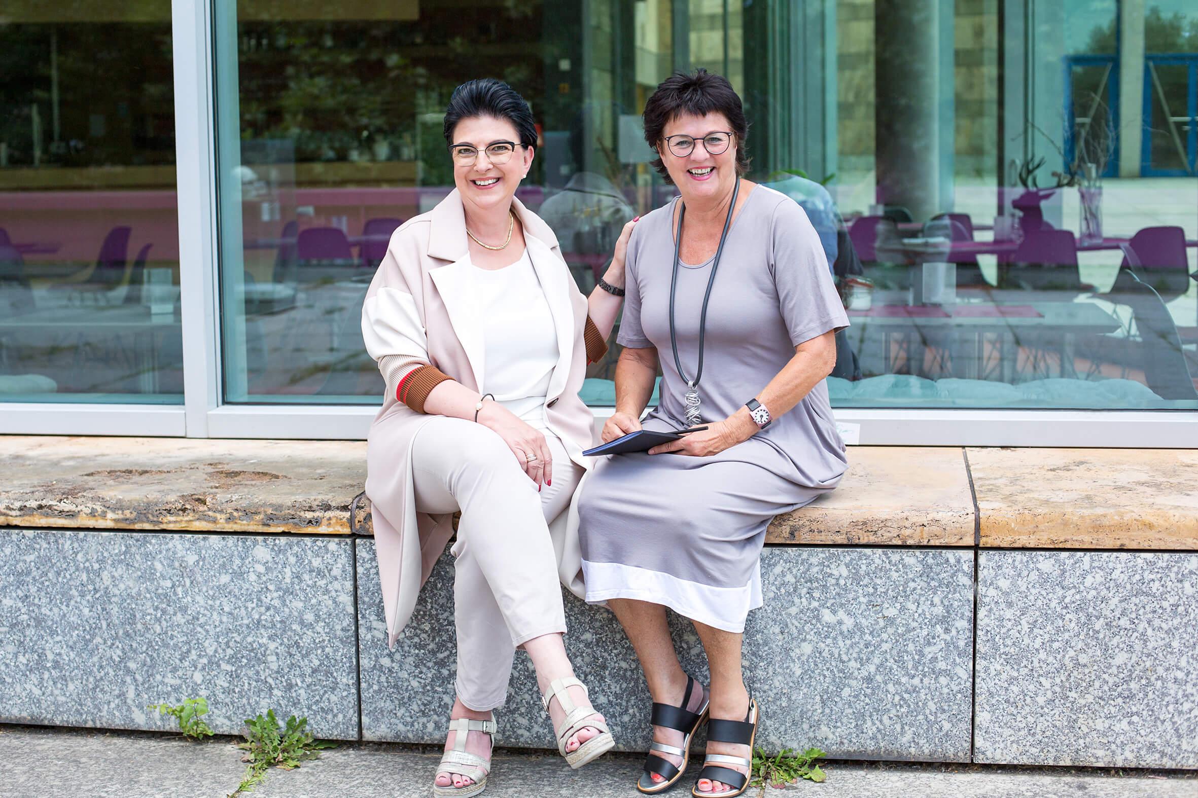 2 Frauen sitzen vor einem Café